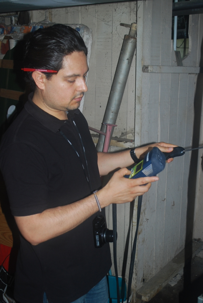 SDC Energy Auditor Javier Ortiz checks the efficiency of a furnace during a home energy audit.