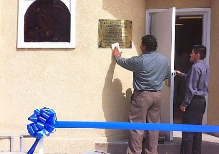 A volunteer shines the La Luz del Mundo Family Services sign outside at the center before the event.