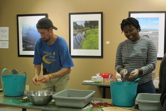 Walnut Way employees Jeremy Davis, environmental specialist and Alexandria Barnett, healthy store coordinator, cut peppers for canning and preserving at Urban Ecology Center-Riverside Park. (Photo by Shakara Robinson)