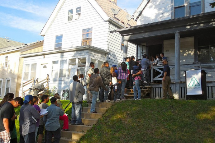 Families line up outside 1212 S. 26th St. to take a tour of the three-bedroom house.