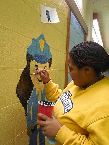 "Sydney Lawrence, 19, paints a policewoman in the ""hallway of professions,"" which is meant to inspire students to think about their career goals. (Photo by Maria Corpus)"