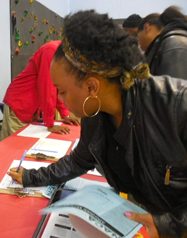 Tanesha Howard signs up to receive information from National Assistance Corporation of America, one of the many organizations at the resource fair. (Photo by Maria Corpus)