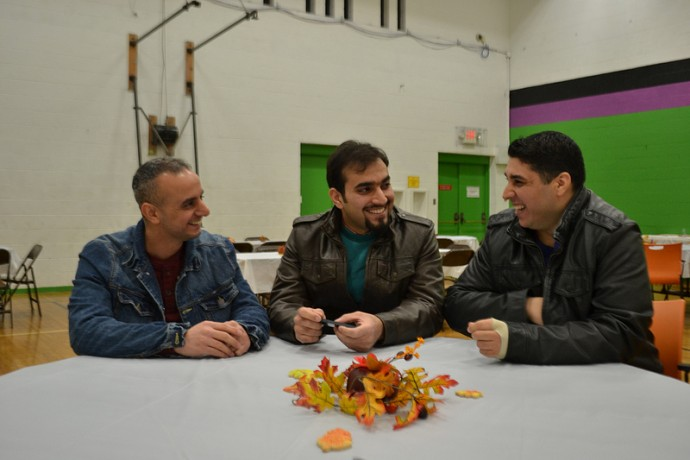 Mohammed Ezzat (left), and Iraqi refugee Anas Aldoori (center) talk to Ili Maikki (right), who came to Wisconsin as a refugee from Malatya, Turkey, in September. (Photo by Tom Momberg)
