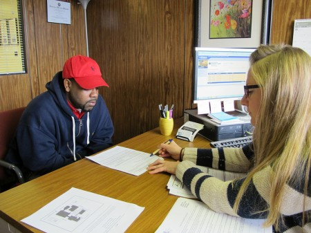 Supervisor Angela Catania explains how to regain a driver's license to Hakim Fudge, who has 15 unpaid tickets, at the Center for Driver's License Recovery and Employability. (Photo by Rick Brown)