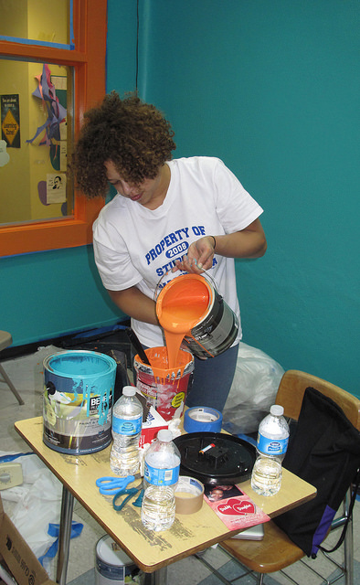 "Hilary Wilson, a volunteer from Harambee Great Neighborhood Initiative, pours some orange paint to finish painting the ""Dream Room."""