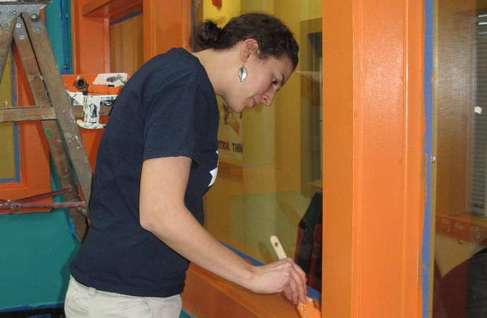 Amanda Schick, a volunteer from Johnsons Park Neighborhood Association, applies a second coat of paint to the dream room. (Photo by Kelly Meyerhofer)