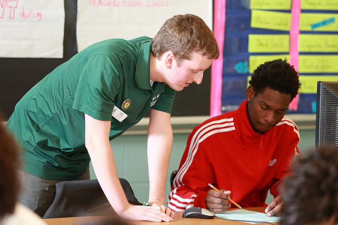 A College Possible coach works with a high school student. (Photo courtesy of College Possible)