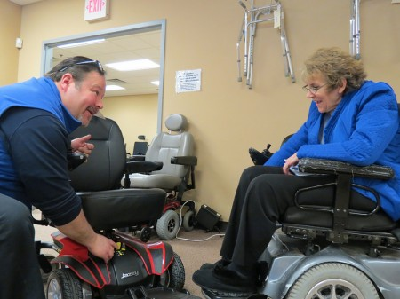 IndependenceFirst sales representative Michael Vigil and customer Robyn Turtenwald discuss the capabilities of Turtenwald's power chair. (Photo by Natalie Wickman)