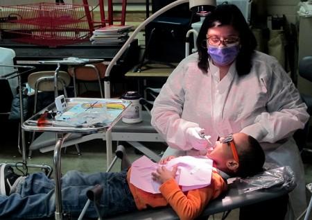 Dental hygienist Geri Travia cleans Corey Wilson's teeth. (Photo by Andrea Waxman)