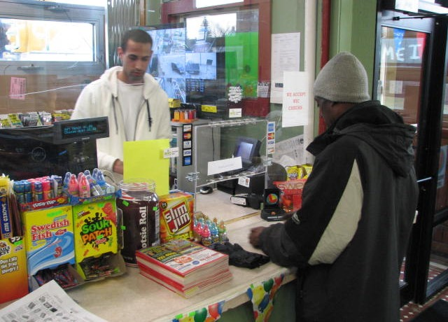 Arshpreet Natt helps a customer at Natt Groceries, 401 N. 35th St., a store he owns with his father Jaswinder. (Photo by Brendan O'Brien)