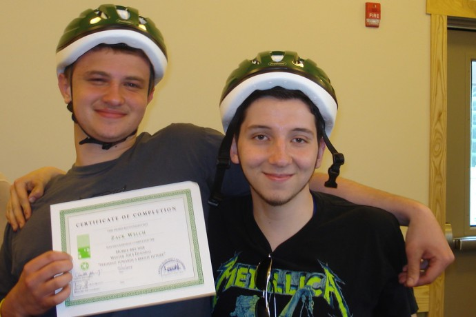 (From left) Participants Zack Welch and Cesar Becerra show off their helmets and certificates after the graduation ceremony. (Photo by Kelly Meyerhofer)