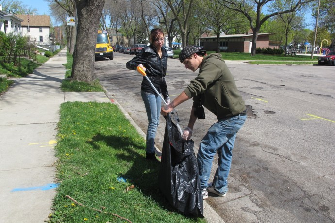 MATC student Sarah Orchel and Youth Build worker Owen Stark team up to clean an area near Clarke Square Park, 2330 W. Vieau Place, last spring. (File photo by Edgar Mendez)
