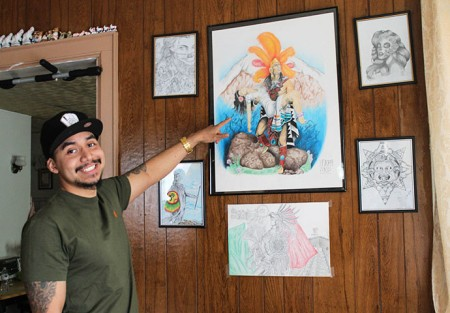 Lawrence Madrigal points to a piece of his original art. (Photo by Madeline Pieschel)