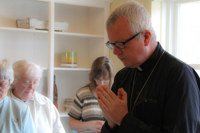 Auxiliary Bishop for the Archdiocese of Milwaukee Donald J. Hying leads friends and supporters of the Clare Community project in prayer at a celebration of the new women's shelter.  (Photo by Karen Slattery)