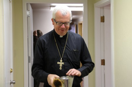 Bishop Donald J. Hyling walks through the new Clare Community apartment sprinkling holy water to bless the new facility.  (Photo by Karen Slattery)