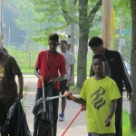 Teens pick up garbage in their neighborhood, employed by community activist Andre Lee Ellis. (Photo by Karen Stokes)