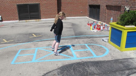 A student plays hopscotch on the newly painted playground. (Photo by Patrick Leary)