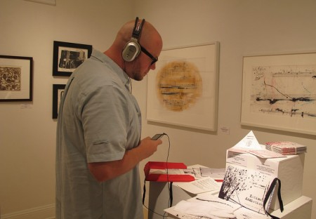A visitor to the exhibit observes the work of Amanda Schoofs. (Photo by Brittany Carloni)