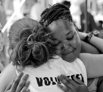 Blaire White (facing camera) embraces volunteer Alida Cardos Whaley at the 2nd Annual Community Event. (Photo by Montreal Cain; courtesy of Community Connections)