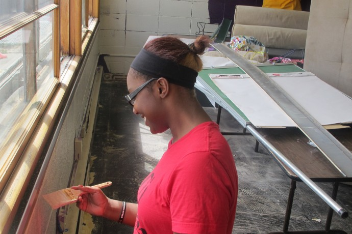 Volunteer J'bri Seay helps paint a second-floor room at Urban Underground. (Photo by Andrea Waxman)