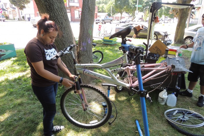 Diana Gutierrez works on a bicycle as part of her internship with the Mobile Bike Hub. (Photo by Layton Boulevard West Neighbors)