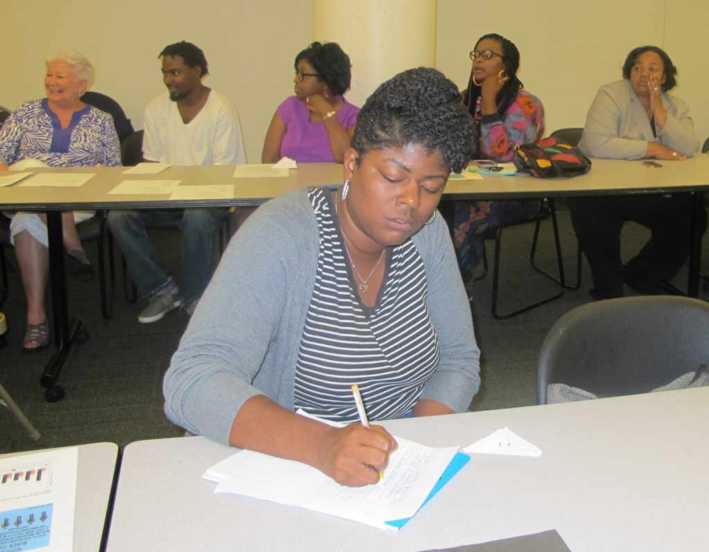 A woman takes notes at a meeting sponsored by the African-American Civic Engagement Roundtable. (Photo by Raina J. Johnson)