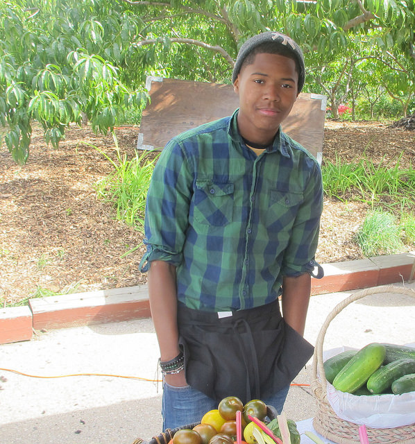 Cameron Nash, an intern for the Garden 2 Market program, sells fresh produce grown in Walnut Way gardens at Harvest Day. (Photo by Molly Rippinger).