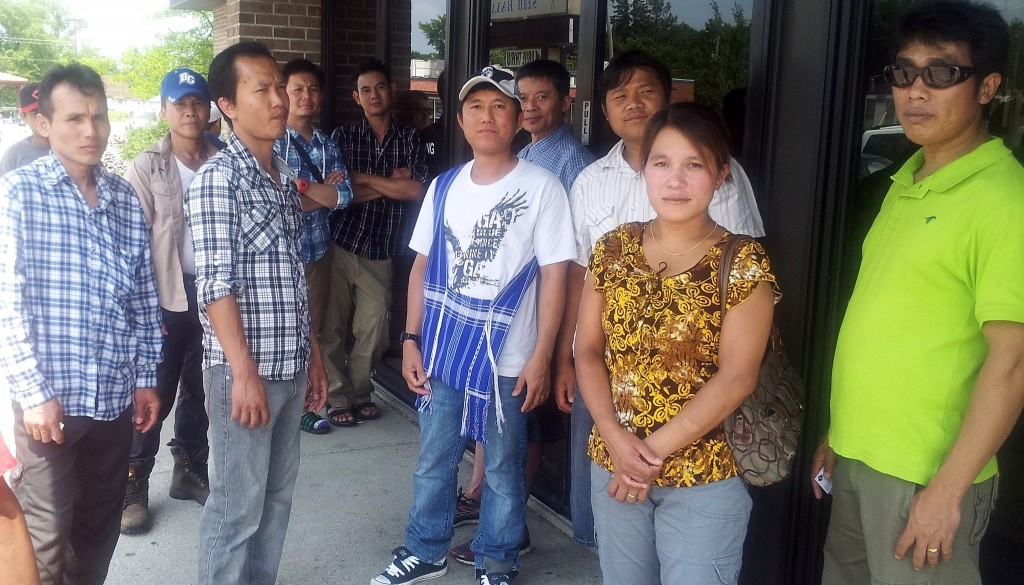 A group of Burmese workers waits outside the American Serb Hall, 5101 W. Oklahoma Ave., to get information about the Cargill beef slaughterhouse plant closing. (Photo by Edgar Mendez)