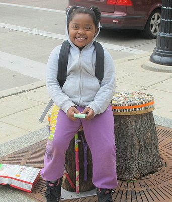 "Jasmine Johnson made use of a colorful ""LUV"" seat while waiting for the bus with her mother, Deborah."
