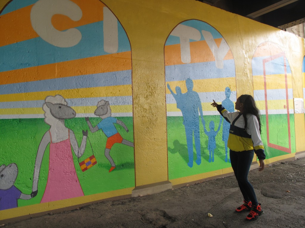 A Silver City Town House resident mirrors a figure on a new mural at 35th Street and National. (Photo by Teran Powell)