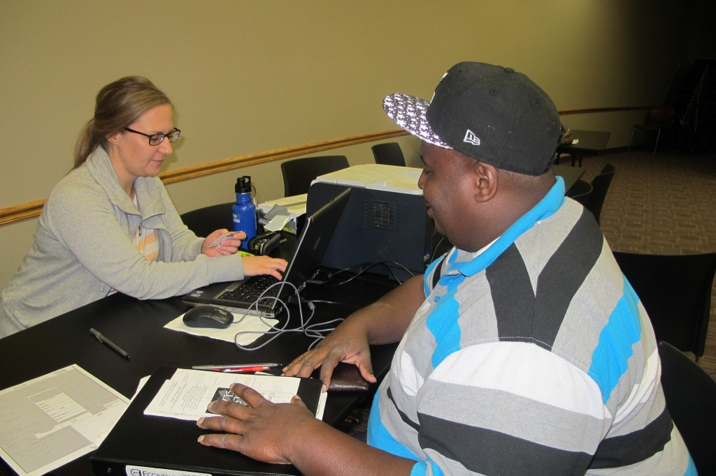 Jermaine Jackson works with Angela Catania, a supervisor at the Center for Driver's License Recovery and Employability, to check his driving status.