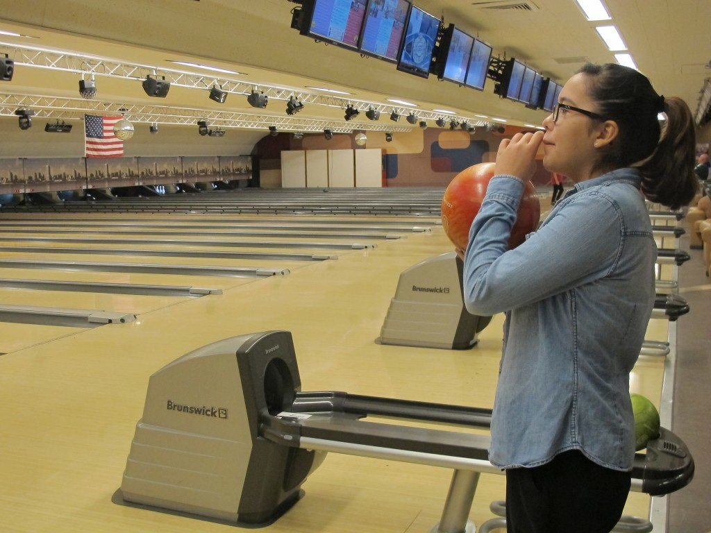 Ana Loppnow, 14, checks the score and gets set to bowl her first frame of the day against her brother and sister. (Photo by Teran Powell)