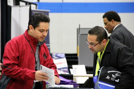 Javier Ortiz (left), an energy auditor with the Social Development Commission, discusses weatherization strategies with Emmanuel Oquendo (right). (Photo by Molly Rippinger)
