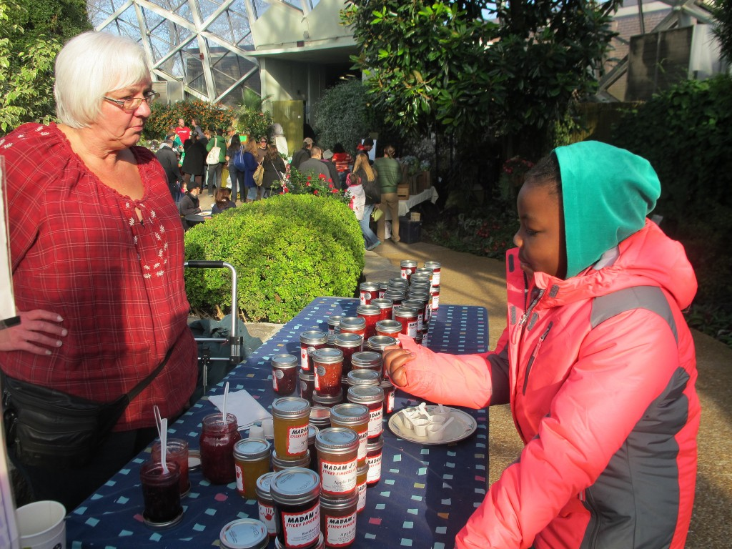 Jeanine Baker of Madam J's Sticky Fingers Jams and Jellies listens as a young girl asks about the flavors of her products. (Photo by Teran Powell)