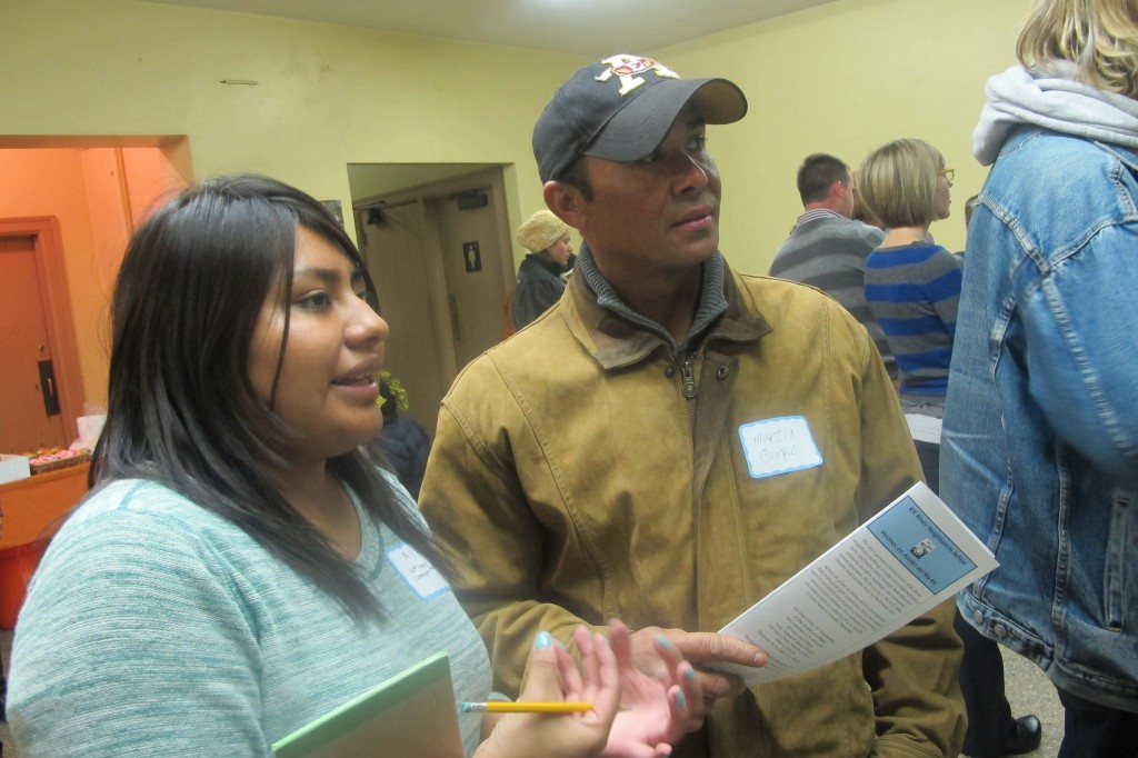 Alex Hernandez (left) provides information about revitalization efforts to neighborhood resident Martin Carpio at a recent open house at the Pulaski pavilion. (Photo by Edgar Mendez)