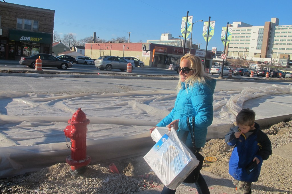 Ariane Fischer, walking along South 27th Street with her son Samuel, said the construction has caused her to take fewer trips to shops in the area. (Photo by Edgar Mendez)