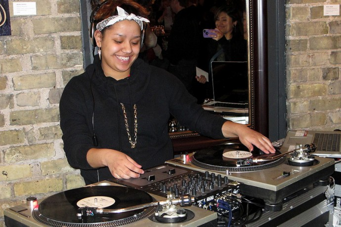"TRUE Skool teen Jaylen ""DJaylen"" Perez sets the mood with her music selections at the opening of the exhibit ""Well-Behaved Women: Journeys to Fearlessness."" (Photo by Andrea Waxman)"