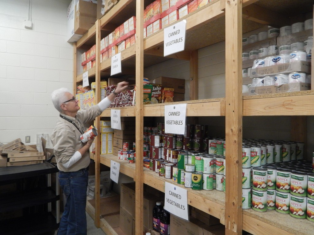 Al Luzi said the Agape Community Center food pantry stocks everything from canned food to personal care products. (Photo by Caroline Roers)