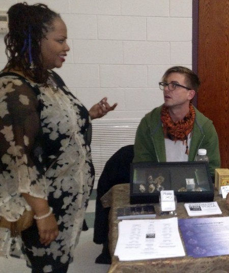 Market organizer Angela Smith chats with vendor Nick Sweet of Prana Wellness on Wells. (Photo by Robyn St. John)