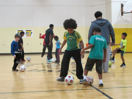 With the help of coaches, players practice shuffling soccer balls between their feet. (Photo by Teran Powell)